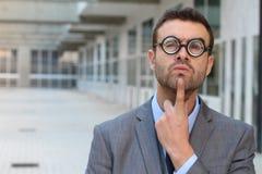 Zadumana mądra samiec z bardzo gęstymi eyeglasses zdjęcie stock