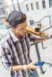 Zadumana męska łyżwiarki przesyłanie wiadomości na telefonie Obrazy Royalty Free