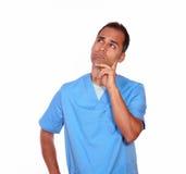 Zadumana męska pielęgniarki pozycja z ręką na podbródku Fotografia Stock