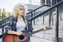 Zadumana młoda afro amerykańska dziewczyna samotnie na miasto ulicznej bawić się gitarze zdjęcia stock