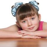 Zadumana młoda dziewczyna przy biurkiem fotografia stock
