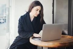 Zadumana młoda kobieta pracuje na laptopie w kawiarni zdjęcie stock