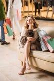 zadumana młoda kobieta w futerkowego żakieta obsiadaniu z torba na zakupy zdjęcie royalty free