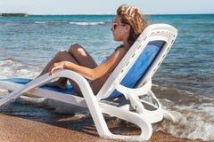 Zadumana młoda kobieta w okularach przeciwsłonecznych siedzi w deckchair, aga Zdjęcia Stock