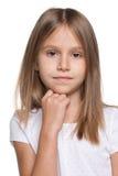 Zadumana mała dziewczynka przeciw białemu tłu zdjęcia royalty free