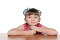 Zadumana mała dziewczynka przy biurkiem fotografia stock