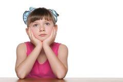 Zadumana mała dziewczynka przy biurkiem zdjęcie stock
