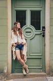 Zadumana przyglądająca kobieta stoi outdoors przeciw drzwi Fotografia Royalty Free