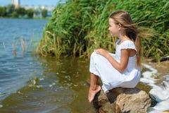 Zadumana romantyczna mała dziewczynka w biel sukni blisko rzeki obraz royalty free