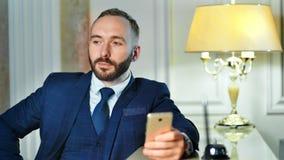 Zadumana uśmiechnięta męska biznesmena writing wiadomość używać smartphone blisko recepcyjnego biurka przy hotelem zbiory wideo