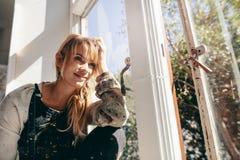 Zadumanego żeńskiego artysty brudny obsiadanie i patrzeć z okno Obrazy Stock