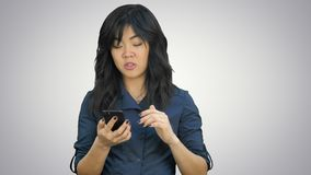 Zadumanego azjatykciego bizneswomanu czytelnicza prezentacja na smartphone, patrzeje kamerę na białym tle zbiory wideo