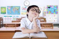 Zadumanego małego ucznia myślący pomysł w klasie obrazy royalty free