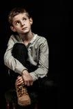 Zadumanej młodej chłopiec siedzący główkowanie Zdjęcia Stock