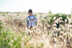 Zadumani chłopiec stojaki w polu wśród rośliien obraz stock