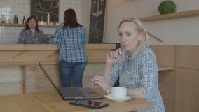 Zadumany żeński blogger pracuje na laptopie w kawiarni zbiory