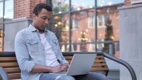 Zadumany afrykański mężczyzna pracuje na laptopie, siedzi na ławce zdjęcie wideo