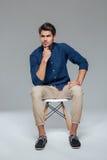 Zadumany atrakcyjny przypadkowy młodego człowieka obsiadanie na krześle obrazy stock