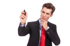 Zadumany biznesowy mężczyzna writing jest coś Zdjęcie Royalty Free