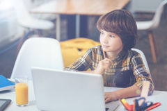 Zadumany chłopiec obsiadanie przy laptopem i marzyć Obraz Stock