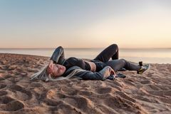 Zadumany dorosły dziewczyny lying on the beach na piasku na plaży przy zmierzchem dzień jest ubranym czerni ubrania fotografia royalty free