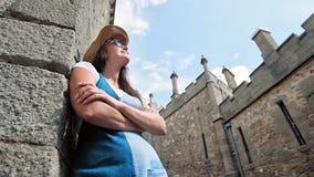 Zadumany kobieta wycieczkowicz stoi opartą kamienną ścianę z krzyżującym ręki architektury turystycznym miejscem zbiory