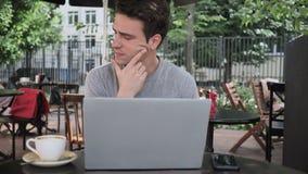 Zadumany mężczyzna główkowanie, działanie na laptopu obsiadaniu w kawiarnia tarasie i zbiory