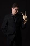 Zadumany mężczyzna jest ubranym czarnego kostiumu mienia w jeden ręce zwierzęca czaszka Zdjęcia Stock