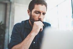 Zadumany mężczyzna używa współczesnego laptop przy biurem zamazujący tło horyzontalny Zdjęcia Stock