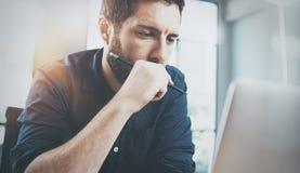 Zadumany mężczyzna używa współczesnego laptop przy biurem zamazujący tło horyzontalny racy Fotografia Royalty Free