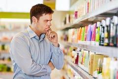 Zadumany mężczyzna w supermarketa robić Zdjęcia Stock