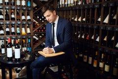 Zadumany mężczyzny sommelier pisze w notepad coś przy barem z krzyżować nogami fotografia royalty free