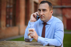 Zadumany męski pracownik używa telefon dla komunikaci Fotografia Stock
