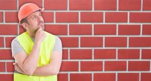 Zadumany młodego człowieka budowniczy z ciężkim kapeluszem fotografia stock