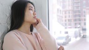 Zadumany młody azjatykci kobiety główkowanie, brainstorming i podczas gdy siedzący przy okno zbiory wideo