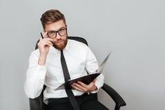 Zadumany młody biznesmen trzyma falcówkę w eyeglasses zdjęcie royalty free