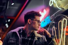Zadumany młody człowiek opiera na iluminującym signboard w ulicie przy nocą obrazy stock