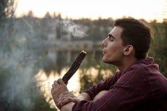 Zadumany młody człowiek z płonącą nazwą użytkowniką chmura dymu na jeziorze kosmos kopii obraz royalty free