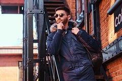 Zadumany młody człowiek z plecak pozycją na schodkach outside zdjęcia royalty free