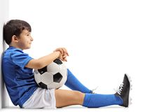 Zadumany mały futbolisty obsiadanie na podłoga i opierać znowu fotografia stock