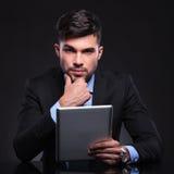 Zadumany młody biznesowy mężczyzna z pastylką Fotografia Stock