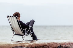 Zadumany Nastoletni na jego krześle Stawia czoło przy oceanem Zdjęcie Stock