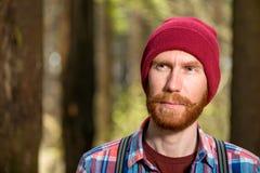Zadumany portret brodaty mężczyzna w czerwonym kapeluszu Zdjęcia Royalty Free