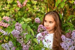 Zadumany portret nastoletnia dziewczyna w lilych krzakach w białej sukni Zdjęcie Royalty Free