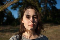 Zadumany portret powabna dziewczyna z cieniem na jej twarzy od sosnowych gałąź zdjęcia stock