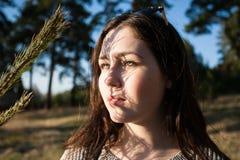 Zadumany portret powabna dziewczyna z cieniem na jej twarzy od sosnowych gałąź obraz royalty free