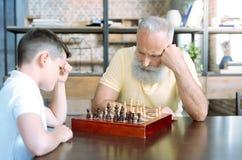 Zadumany starszy mężczyzna i jego wnuk bawić się szachy zdjęcie royalty free