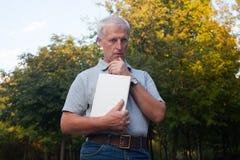 Zadumany stary człowiek z książką zdjęcie stock
