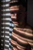 Zadumany toples mężczyzna w cieni lampasach od okno Obraz Royalty Free