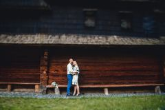 Zadziwiająca ślub para w embroidereds koszulowi z wiązką kwiaty na tle drewniany dom obrazy stock